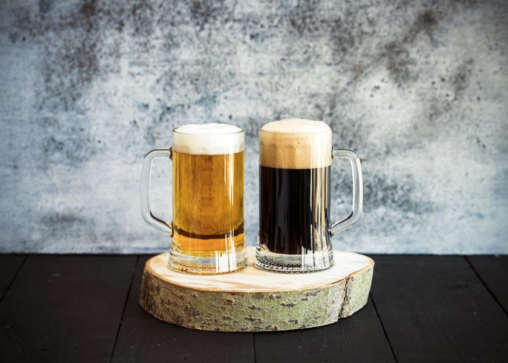 Светлое и темное пиво в кружках на деревянной доске